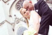Bride and groom in front of the church — Stock Photo