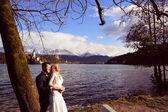 Bride and groom embracing near lake — Foto de Stock