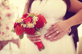 Hands of a bride and groom with red bouquet — Stock Photo