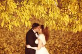 Autumn leaves with bride and groom as silhouettes — Stock Photo