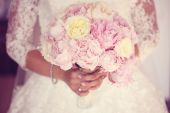 Hands of a bride holding peonies bouquet — Stock Photo
