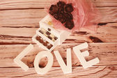 Mini chocolate sweets and LOVE letters — Stock Photo