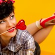 Pin up girl with heart shaped lollipop — Stock Photo #80670798