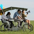 Постер, плакат: Woman leading 4 guys on a quad bike on a green field