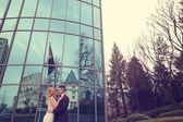 Bridal couple near building made of glass — Stock Photo