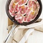 Raw beefsteak & seasoning in pan. wooden bord. on white. — Stock Photo #69805023