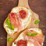 Bruschetta with prosciutto ham & figs with white cheese. fresh b — Stock Photo #69815621