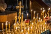 Velas de iluminação de mulher na igreja cristã — Fotografia Stock