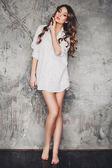 Beautiful young woman in a white men's shirt — Stockfoto