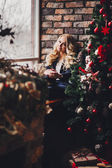 Beautiful young blond woman near the Christmas tree dream — Stockfoto