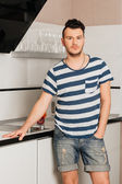 Brunette  with stubble in a striped T-shirt the kitchen — Stock Photo