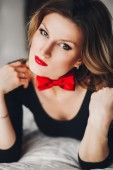 Beautiful girl in black body with red butterfly and lips looking into the camera — Stock Photo