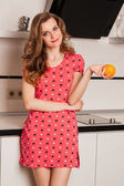 Beautiful girl long hair in the kitchen with orange — Stock Photo