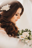Beautiful bride with dark hair and a bouquet — Stock Photo