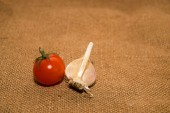 Cherry tomato and garlic on old cloth — Stock Photo