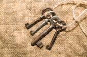 Four  very old keys tied with a rope on old cloth — Stock Photo