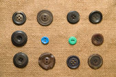 A lot of old buttons  on the old cloth — Stock Photo
