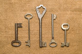Four old keys to the safe on a very old cloth — Stock Photo