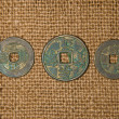 Ancient Chinese bronze coins on old cloth — Stock Photo #71513559