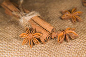 Star anise and cinnamon sticks on old cloth — Stock Photo