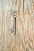 Old key from the lock on a wooden texture — Stock Photo