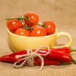 Red cherry tomatoes in a yellow cup and Chile peppers  on old cl — Stock Photo #73835743