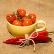 Red cherry tomatoes in a yellow cup and Chile peppers  on old cl — Stock Photo #73835765
