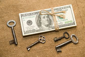 One pack of dollars and keys on an old cloth — Stock Photo