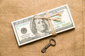 One pack of dollars and key on an old cloth — Stock Photo