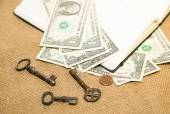 Opened notebook, keys and money on the old tissue — Stock Photo