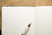 Opened notebook and pen on the old tissue — Foto Stock