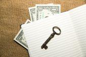 Caderno aberto, chave e dinheiro sobre o tecido velho — Fotografia Stock