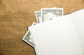 Opened notebook and money on the old tissue — Stock Photo