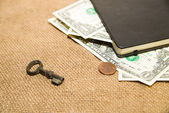 Notebook, key and money on the old tissue — Stock Photo
