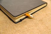 Notebook and pencil on the old tissue — Stock Photo