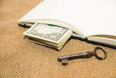 Opened notebook, key and money on the old tissue — Stock Photo