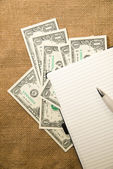 Opened notebook, pen and money on the old tissue — Stock Photo
