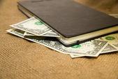 Notebook e dinheiro sobre o tecido velho — Fotografia Stock