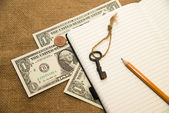 Opened notebook, pencil, key and money on the old tissue — Stock Photo