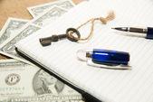 Geopend van notitieblok-, pen-, sleutel- en geld op de oude weefsel — Stockfoto