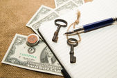 Opened notebook, pen, keys and money on the old tissue — Stock Photo