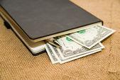 Notebook, pen en geld op de oude weefsel — Stockfoto