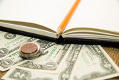Opened notebook, pencil and money on the old tissue — Stock Photo