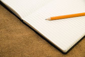 Opened notebook and pencil on the old tissue — Stock Photo
