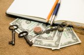Opened notebook, pencil, pen,  key and money on the old tissue — Stock Photo