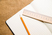 Notepads, pencil and wooden ruler on the old tissue — Stock Photo