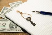 Открыл блокнот, ручка, ключ и деньги на старой ткани — Стоковое фото