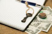 Öppnade notebook, penna, nyckel och pengar på den gamla vävnaden — Stockfoto