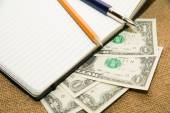 Opened notebook, pencil, pen and money on the old tissue — Stock Photo
