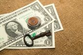 US dollars banknotes, coins and key on an old cloth — Stock Photo